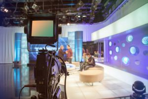 39273022 - television studio with camera and lights - recording tv show. shallow depth of field - focus on camera